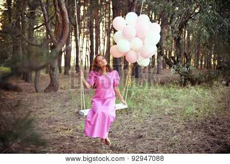 Young woman in pink retro dress is swinging on a swing in summer pine forest. Image toned and noise added.