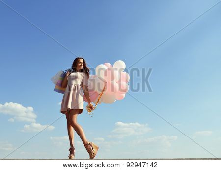 Beautiful girl holding shopping bags and colored balloons over blue sky