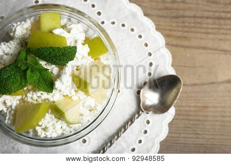 Cottage cheese with green apple on wooden table, closeup