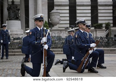 NEW YORK - MAY 21 2015: Members of the US Coast Guard Ceremonial Honor Guard Silent Drill Team kneel down during a drill next to the New York Public Library in Bryant Park during Fleet Week NY 2015.