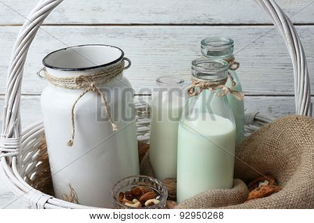 Milk in glassware with walnuts and cookies on wooden background