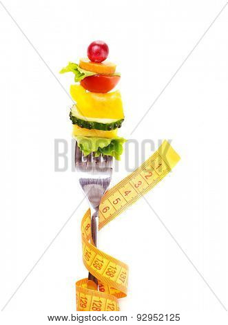 Snack of vegetables on fork with measuring tape isolated on white