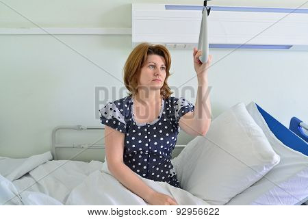 Female Patient Holding On To Device For Lifting In Hospital Room