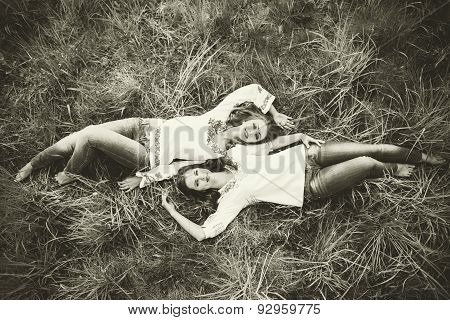 Two Happy Pretty Girls Lying On The Grass