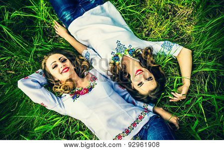 Two Happy Pretty Girls Lying On The Green Grass