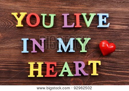 Inscription YOU LIVE IN MY HEART made of colorful letters on wooden background