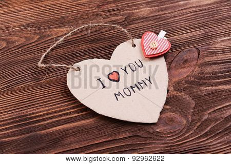 Inscription I LOVE YOU MUMMY on cutout carton on wooden background