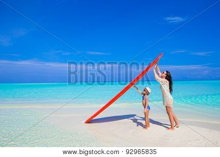 Happy woman and little girl at white beach with surfboard