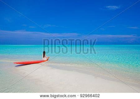 Young surfer woman at white beach on red surfboard