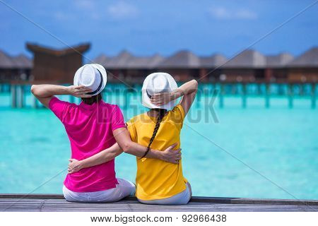 Young couple on beach jetty at tropical island in honeymoon