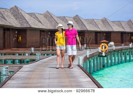 Happy couple on tropical beach jetty going to the beach at Maldives