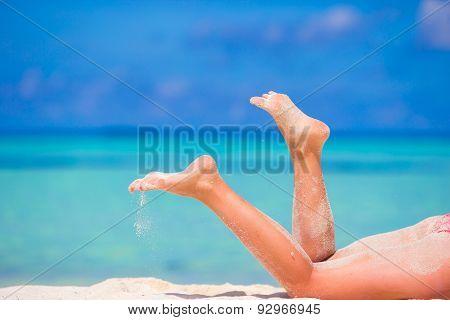Woman's beautiful slim tanned legs on white beach