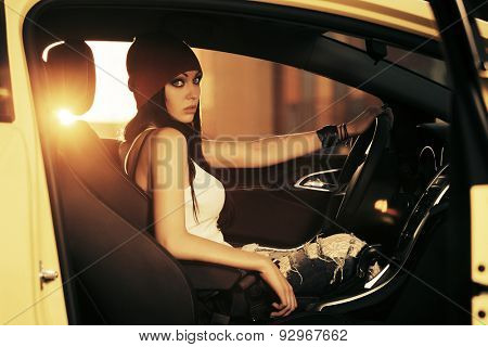 Young gorgeous fashion woman sitting in a car