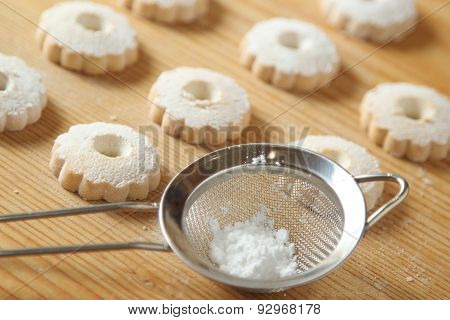 Italian Canestrelli Cookies And A Strainer With Powdered Sugar