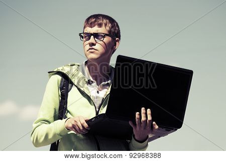 Young fashion man using laptop outdoor
