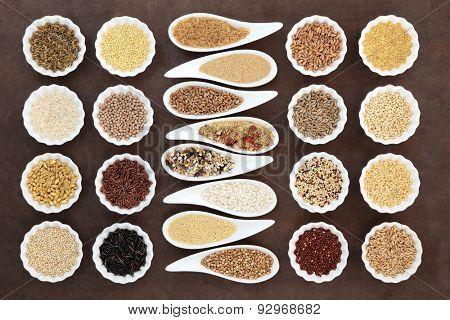 Grain and cereal food selection in porcelain bowls over lokta paper background.
