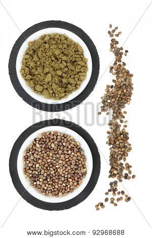 Hemp seed and powder in porcelain bowls on grey slate and loose over white background.