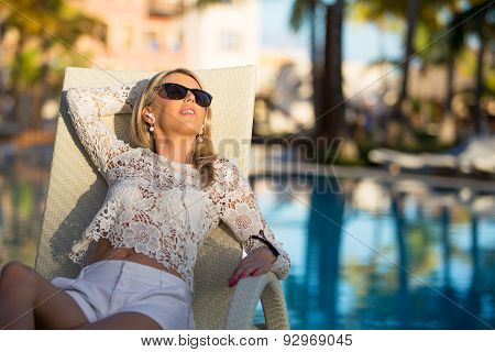 Woman lying in deck chair by the pool
