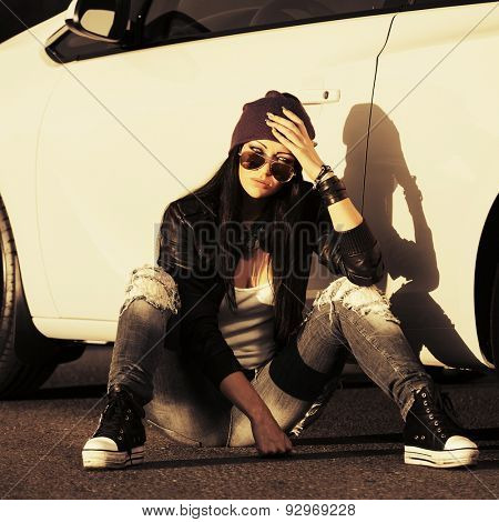 Sad young stylish fashion woman in sunglasses sitting by her car outdoor