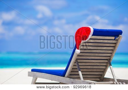 Sun chair lounge with red Santa Hat on tropical white beach and turquoise water