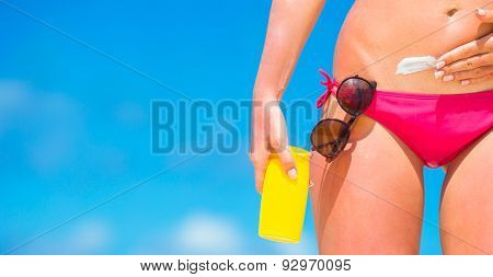 Closeup applying with sunscreen on white beach