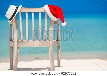 Red santa hat and white straw hat on beach chair at tropical vacation