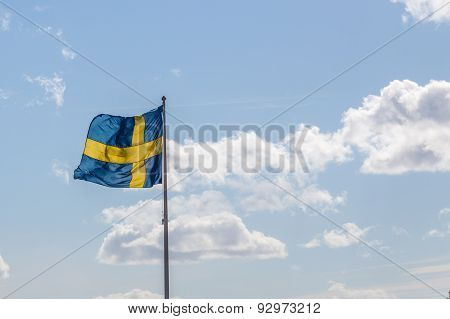 Swedish Flag Waving In Front Of Cloudy Sky
