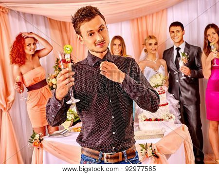 Group people at wedding table with cake. Guest says toast.