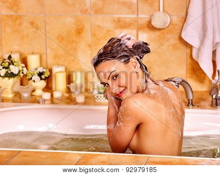 Woman washes her head at home bathroom. Water in bath.