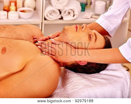Man getting facial  and neck massage in beauty spa.