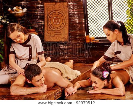 Couple  having oil spa treatment. They hold hands.