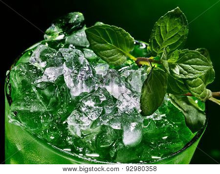 Green drink  with crushed ice on dark background. Top view of close up.