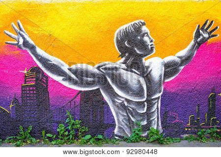 Moscow, Russia - 07 June 2015: Street Art Graffiti Of Body Builder Man On A Colorful Cityscape On Th