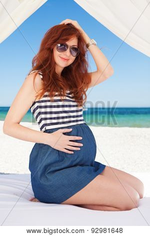 Pregnant fashion woman relaxing on the beach