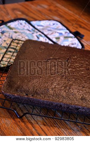 Chocolate Cake Cooling On Rack On Wooden Table