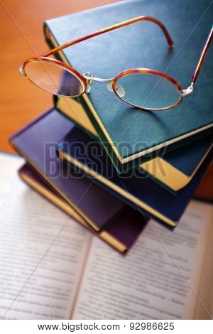 Pile of old books and a pair of vintage glasses on top