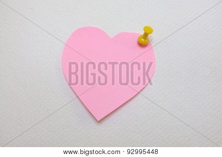 Note paper in heart shape with yellow pin posted on white cork board background