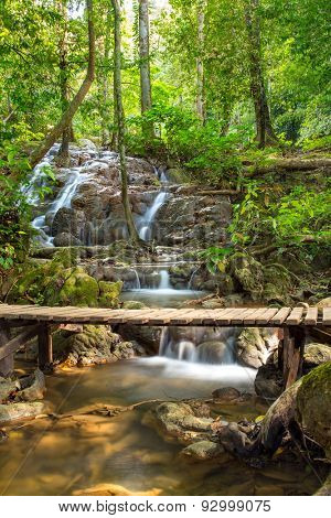 Tropical rain forest landscape with wooden bridge over the beautiful stream with cascades in Thailand