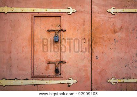 Old rusted padlock hanging on gray metal retro door