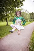stock photo of wig  - Young beautiful girl in irish dance dress and wig jumping outdoor - JPG