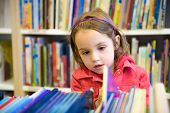 foto of little school girl  - Little girl is choosing a book in the library - JPG
