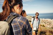 foto of young woman posing the camera  - Young man posing in nature with woman talking his pictures in countryside on a summer day while hiking. Young woman taking photo for her boyfriend with a camera. ** Note: Soft Focus at 100%, best at smaller sizes - JPG