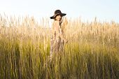 picture of tallgrass  - Sunrise shot of a beautiful young model in tallgrass - JPG