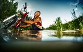 picture of swamps  - Young man athlete with dirty stained clothes crossing the swamp with bicycle - JPG