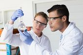 picture of beaker  - Concentrated scientists looking at beaker in laboratory - JPG