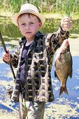 stock photo of fish  - Young fisherman caught fish bream on fishing rod - JPG