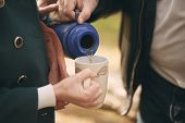 foto of thermos  - Couple in love pours tea from a thermos into the cup to warm up on the street  - JPG