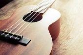 stock photo of ukulele  - Close up of ukulele on old wood background with soft light Vintage tone - JPG