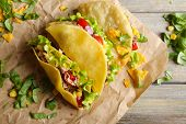 picture of tacos  - Tasty taco with greens on paper on table close up - JPG