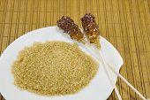 image of sugar  - Two sugar sticks containg white and brown sugar against a wooden table - JPG